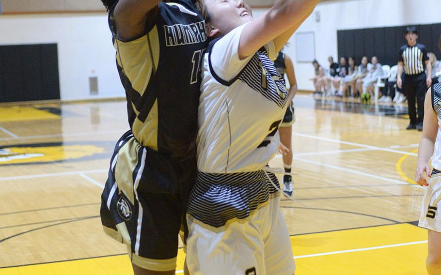 Humphreys' Acacia May leaps over the back of Taejon Christian's Minha Choi for a rebound during Wednesday's Korea Blue girls basketball game. The Blackhawks won 44-17.