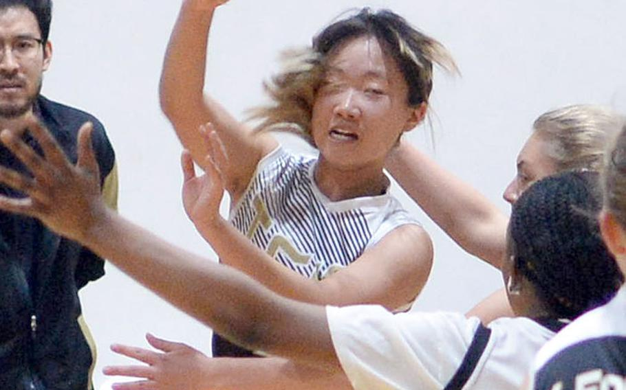 Taejon Christian's Kunlan Yang saves the ball from going out of bounds against Osan during Tuesday's Korea Blue girls basketball game. Yang had 25 points, including the first 21 scored by TCIS, as the Dragons won 34-30.
