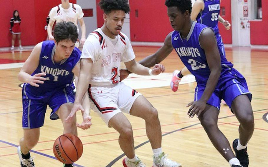 Nile C. Kinnick's James Mincey tries to dribble between Christian Academy Japan defenders during Friday's Kanto Plain boys basketball game. The Knights won 68-64.