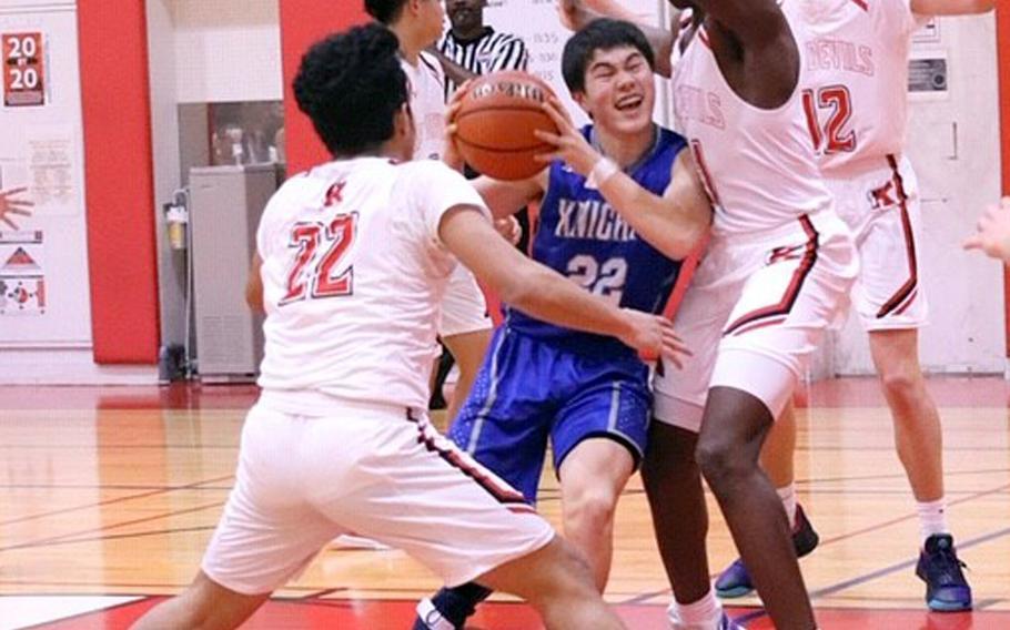 Christian Academy Japan's Koji Matsuoka drives between Nile C. Kinnick defenders during Friday's Kanto Plain boys basketball game. The Knights won 68-64.