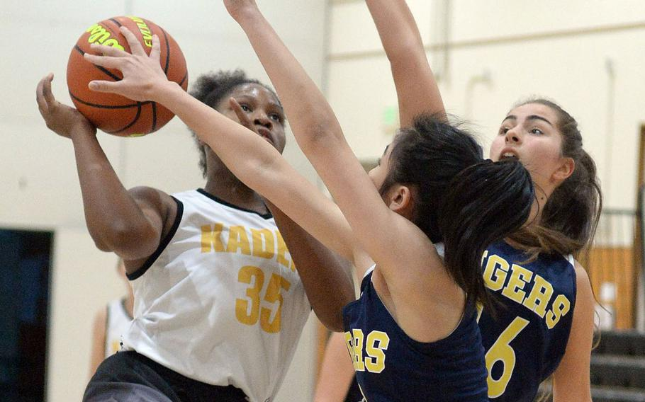 Kadena's Alexis Boyer has her shot blocked by Taipei American defenders during Saturday's Taipei Basketball Exchange girls game. The Tigers routed the Panthers 61-35.