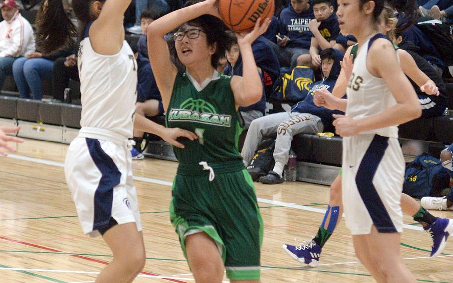 Kubasaki's Urara Williams drives between Taipei American defenders during Saturday's Taipei Basketballl Exchange girls game. The Dragons lost 50-27.