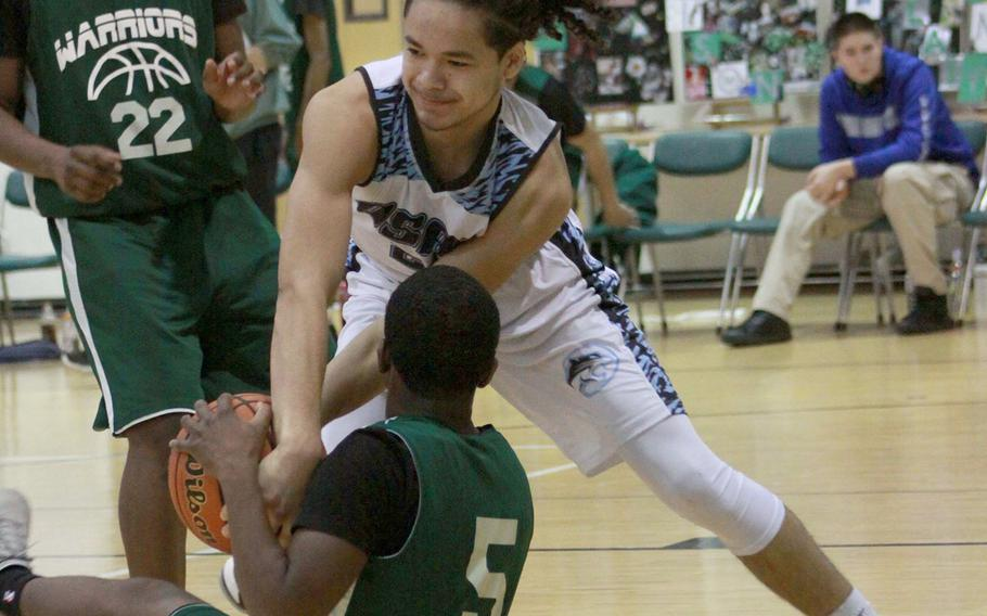 Osan's Israel Rouse and Daegu's Andrue McCall scuffle for the ball as Warriors teammate Antwoine McCall watches during Saturday's Korea Blue boys basketball game. The Cougars won 56-31.
