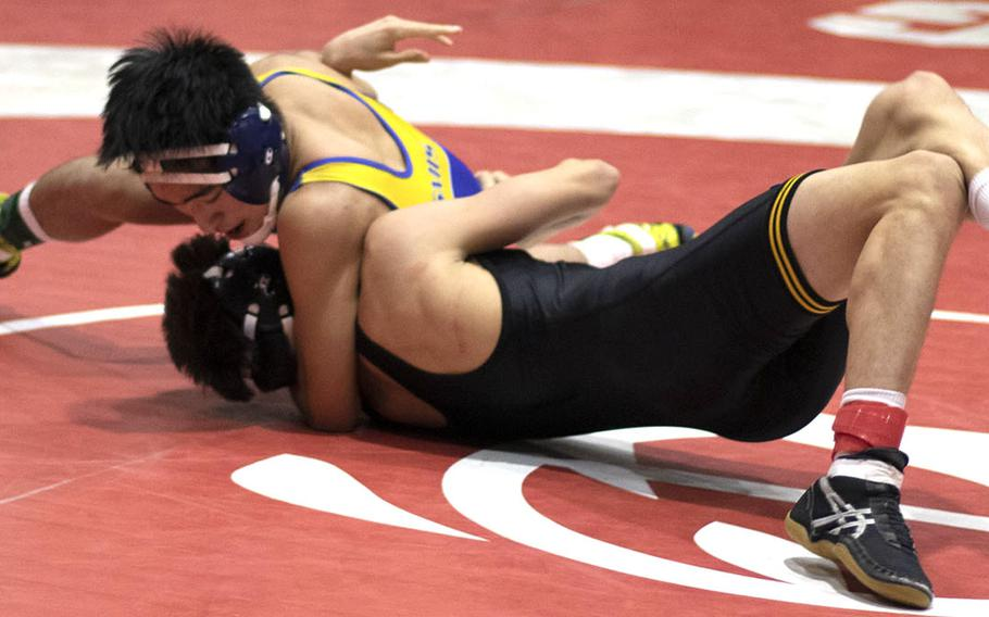 Two-time Far East champion Eiji Kasahara of St. Mary's lands American School In Japan's Take Zoot in the 129-pound final.