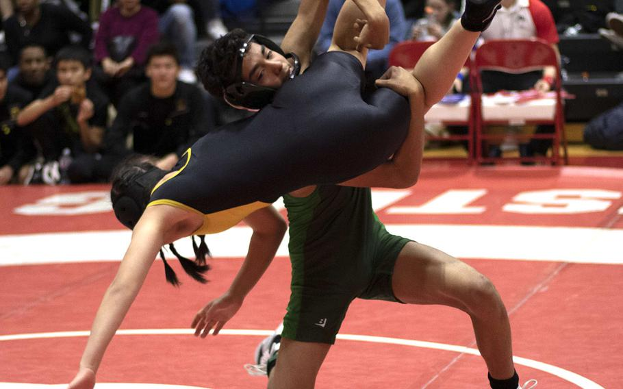 Kubasaki's Nicholaz Aguirre sends Kadena's Mizuki Sato-Marsh flying toward the mat in the 101-pound final. Aguirre won the match and finished in first place.