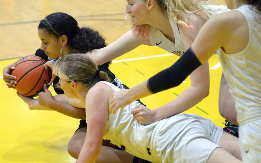 Zama's Fabiola Ayala-Rivera tries to shield the ball from three American School In Japan defenders during Saturday's girls varsity basketball finals game. Zama won the game and the tournament championship.