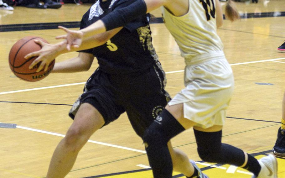 American School In Japan's Cora Eaton reaches in to slow down Zama's Kirari Smith during Saturday's girls varsity basketball finals game. Zama won the game and the tournament championship.