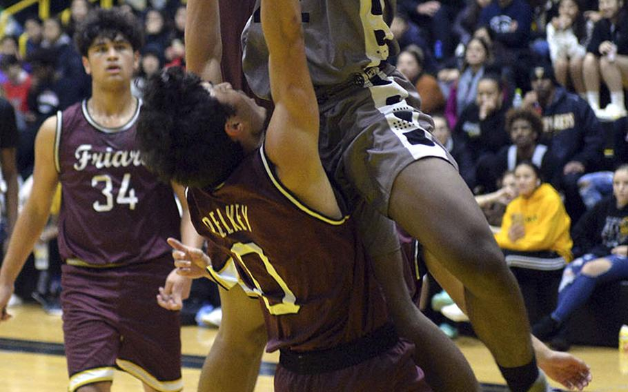 Kadena's John Emery III plows into Father Duenas' Isaiah Pelkey during Saturday's boys varsity finals game. An offensive foul was called on the play. In the end, Father Duenas won the game and the tournament championship.