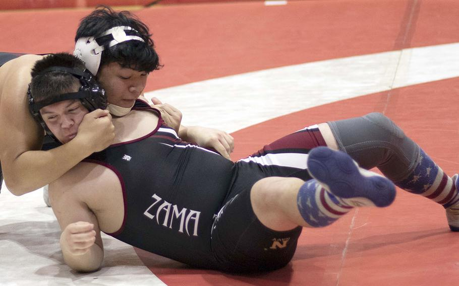 Nile C. Kinnick's Kaleb Leon Guerrero gains the edge on Zama's Josh Petty at 180 pounds during Wednesday's Kanto Plain dual meet. Leon Guerrero won by pin in 2 minutes, 45 seconds and the Red Devils won the meet 47-14.