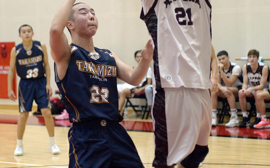 Matthew C. Perry's Joseph Andres shoot past an Iwakuni Takamizu defender during Wednesday's Japan boys basketball game. The Samurai won 77-70.