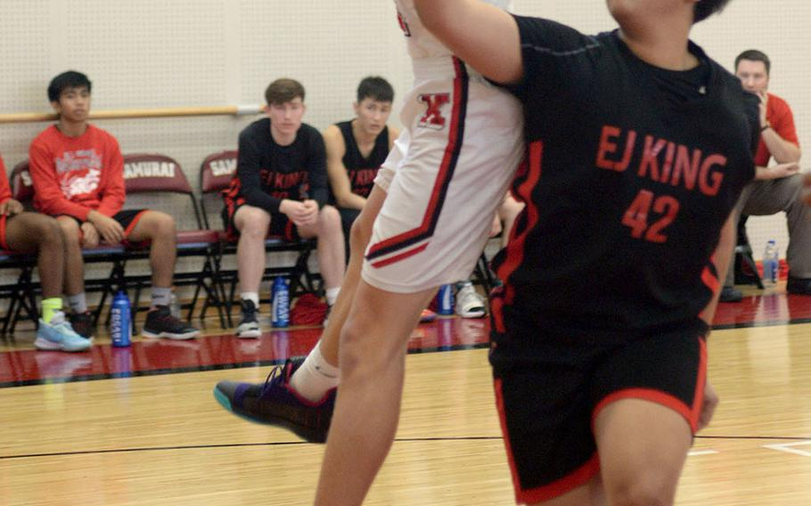 Kinnick's Ethan Yuska leaps for a rebound in front of King's Tsuyoshi Kemp.