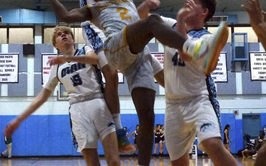 Humphreys' Myles Johnson loses his balance underneath the basket while surrounded by Osan defenders during Saturday's DODEA-Korea Cup boys basketball game. The Blackhawks won the game 72-52.