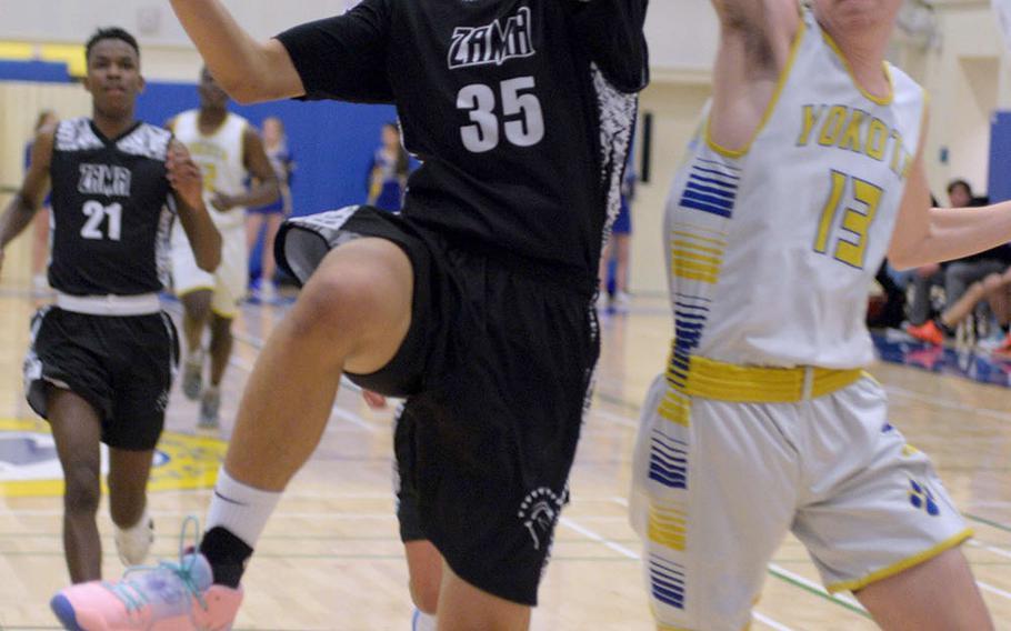Zama's Murray Gillerson shoots past Yokota's Anthony Logue during Tuesday's DODEA-Japan/Kanto Plain boys basketball game. The Trojans won 65-54.