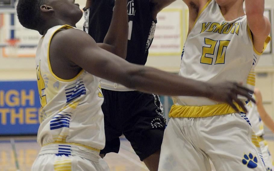 Zama's Terrence Ward has his shot blocked by Yokota's Connor Rowan as teammate C.J. Canada moves in from left during Tuesday's DODEA-Japan/Kanto Plain boys basketball game. The Trojans won 65-54.