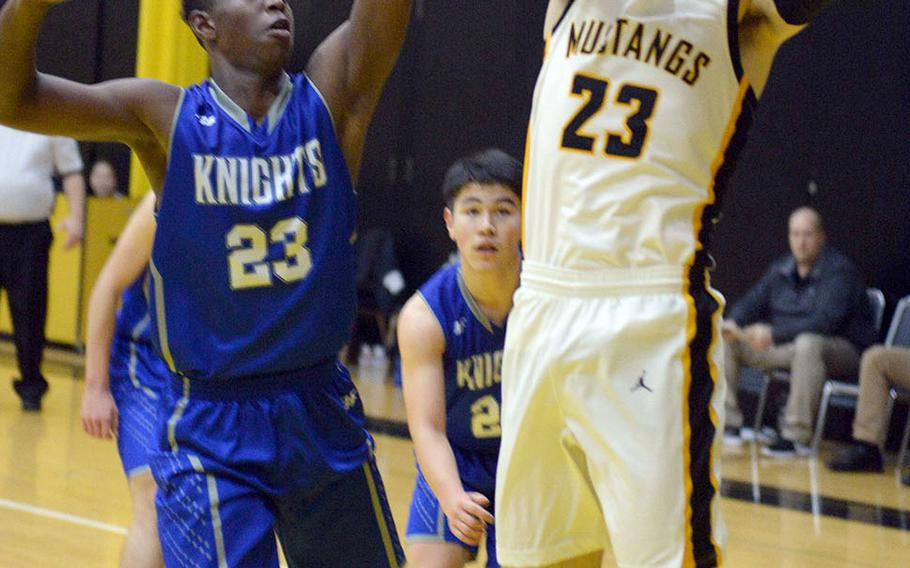 American School In Japan's Adam Knode shoots against Christian Academy Japan's Enosh Mutenda during Wednesday's Kanto Plain boys basketball game. The Mustangs won 49-44,. Knode is a second-generation Mustang; his father, Steve, played for ASIJ in the mid-1980s.
