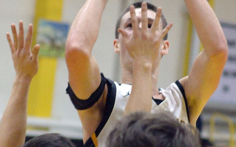 Despite a Christian Academy Japan hand in his face, American School In Japan's Nash Rasmussen gets off a shot during Wednesday's Kanto Plain boys basketball game. The Mustangs won 49-44.