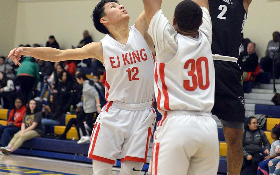 Zama's Kalil Irby shoots over E.J. King's Marcus Schrader and Jalen Nall during Friday's DODEA-Japan boys semifinal, won by the Trojans 62-53.