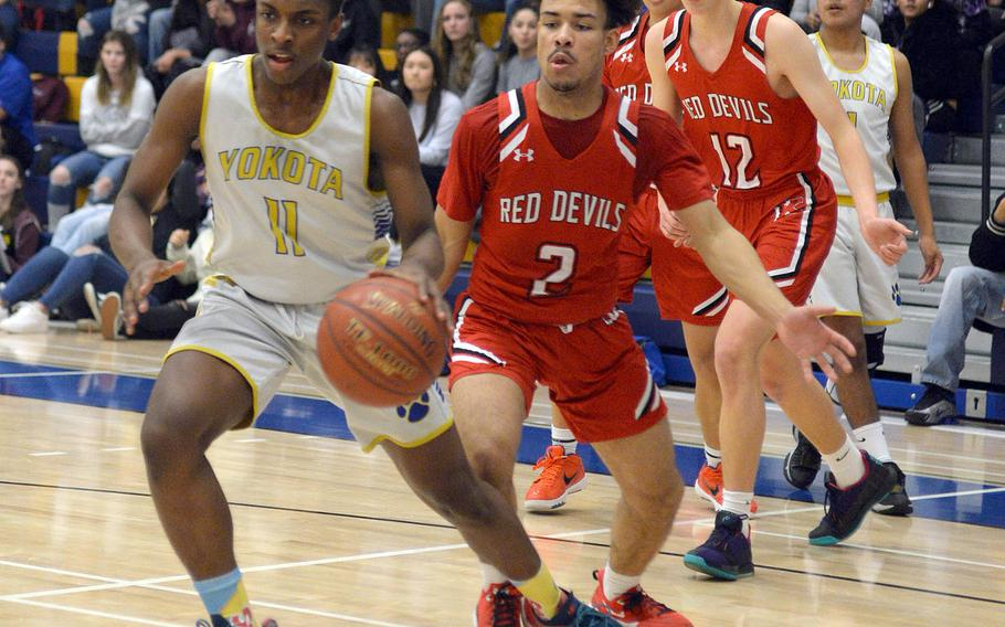 Yokota's Marcus Berrette heads to the basket with Nile C. Kinnick's James Mincey, Ethan Yuska and Tristan Venturina in trail during Friday's DODEA-Japan boys semifinal, won by the Red Devils 68-64.