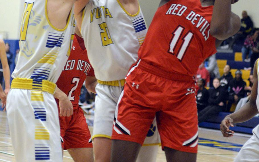 Nile C. Kinnick's Tijari Marshall pulls a rebound away from Yokota's Connor Rowan and Mickey Galvin during Friday's DODEA-Japan boys semifinal, won by the Red Devils 68-64.