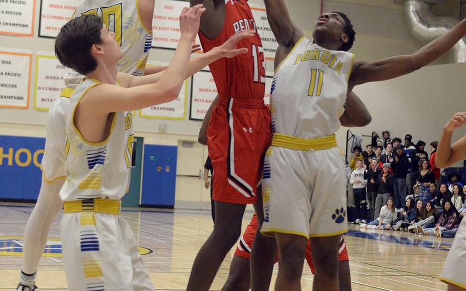 Nile C. Kinnick's Corey Hollingsworth snags a rebound over Yokota's Marcus Berrette, Connor Rowan and Mickey Galvin during Friday's DODEA-Japan boys semifinal, won by the Red Devils 68-64.