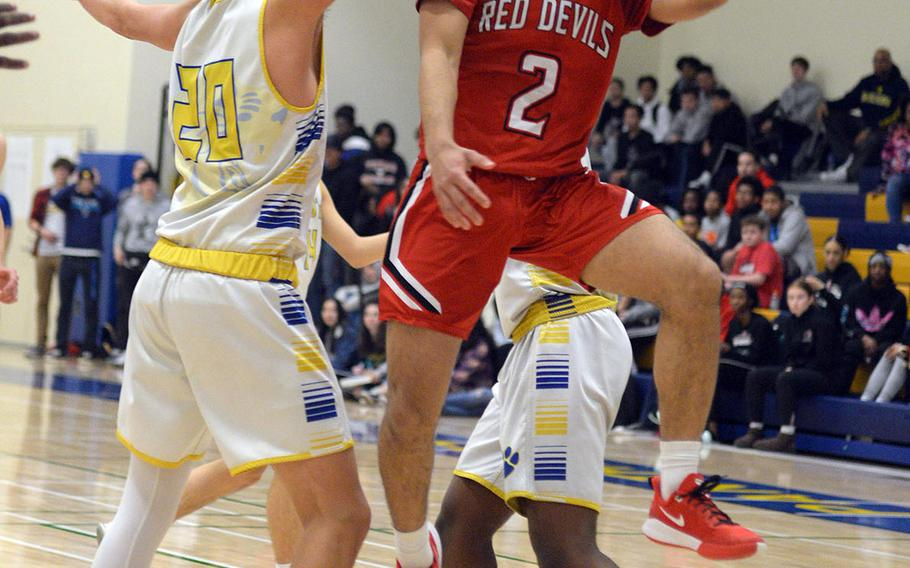 Nile C. Kinnick's James Mincey drives past Yokota's Connor Rowan for a shot during Friday's DODEA-Japan boys semifinal, won by the Red Devils 68-64.