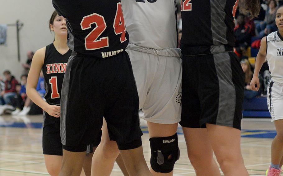 Zama's Jessica Atkinson has her shot contested by Nile C. Kinnick's Dana White and Madelyn Gallo.