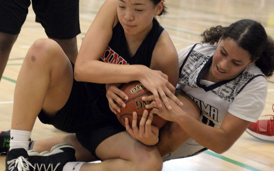 Nile C. Kinnick's Amyka Jones and Zama's Fabiola Ayala-Rivera tie up the ball.