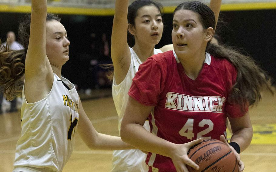 Nile C. Kinnick's Madelyn Gallo drives against two American School In Japan defenders during Tuesday's Kanto Plain girls basketball game. The Mustangs won 36-20.