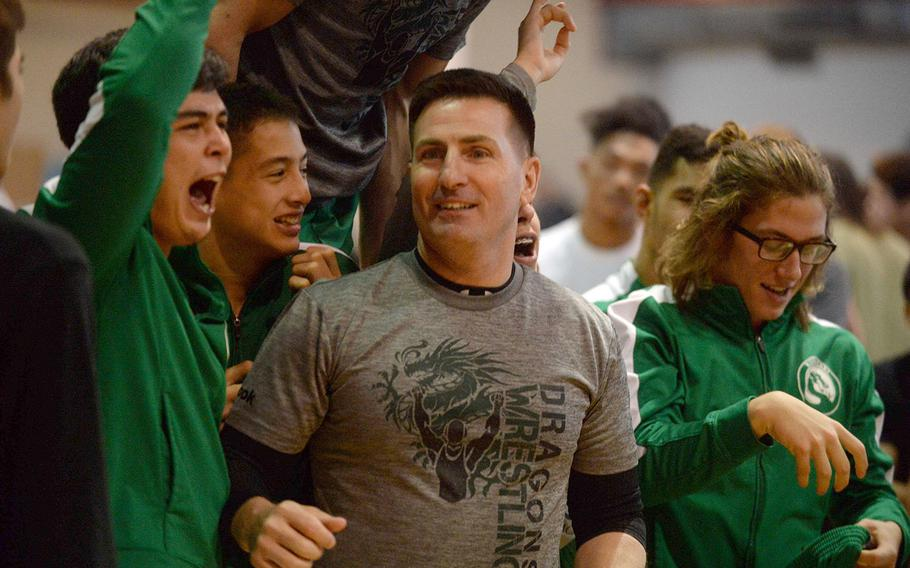 Kubasaki coach Brent Cook and his Dragons celebrate their repeat Far East Division I individual freestyle team title.
