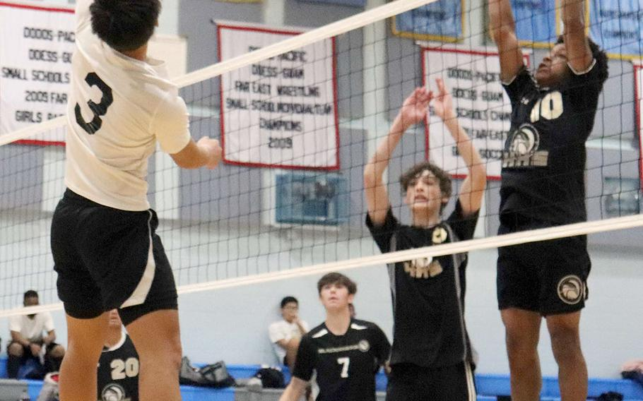 Osan's Anthony Panboon lines up a spike against Humphreys Black's JaKadric Thomas and John Matlock during Wednesday's Korea volleyball. The Cougars won 25-15, 25-12.