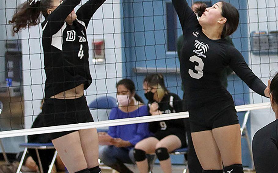 Daegu's Issamoly Thurman and Osan Black's Angela Serrano go up for the ball during Friday's DODEA-Korea girls volleyball. Osan Black beat the Warriors 22-25, 25-23, 25-21.