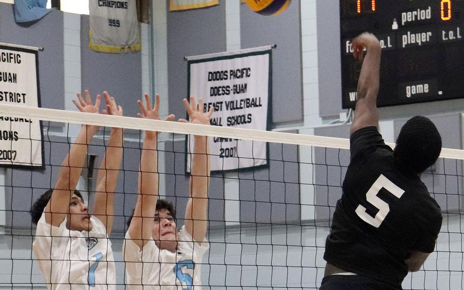 Daegu's Andrue McCall tries to hit past Osan's A.J. Panboon and Sergio DeLuca during Friday's Korea boys volleyball match. The Cougars beat the Warriors 26-24, 25-16.