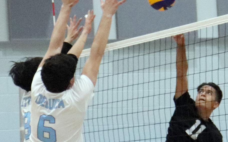 Daegu's Troy Charley tries to hit past Osan's Tim Petrae and Sergio DeLuca during Friday's Korea boys volleyball match. The Cougars beat the Warriors 26-24, 25-16.