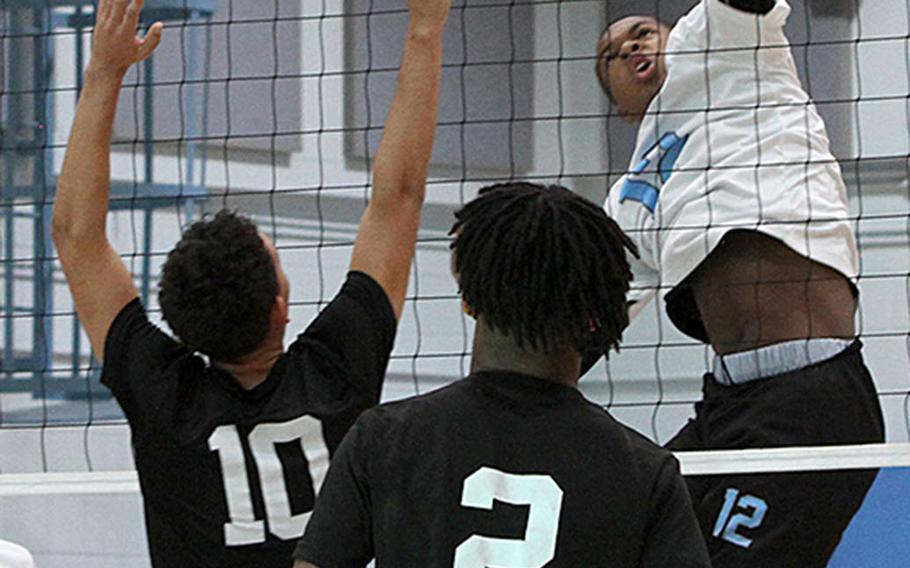 Osan's Tzuriel Jennings spikes against Daegu's Jordan Brown during Saturday's DODEA-Korea boys volleyball match. The Cougars won 25-14, 25-21.