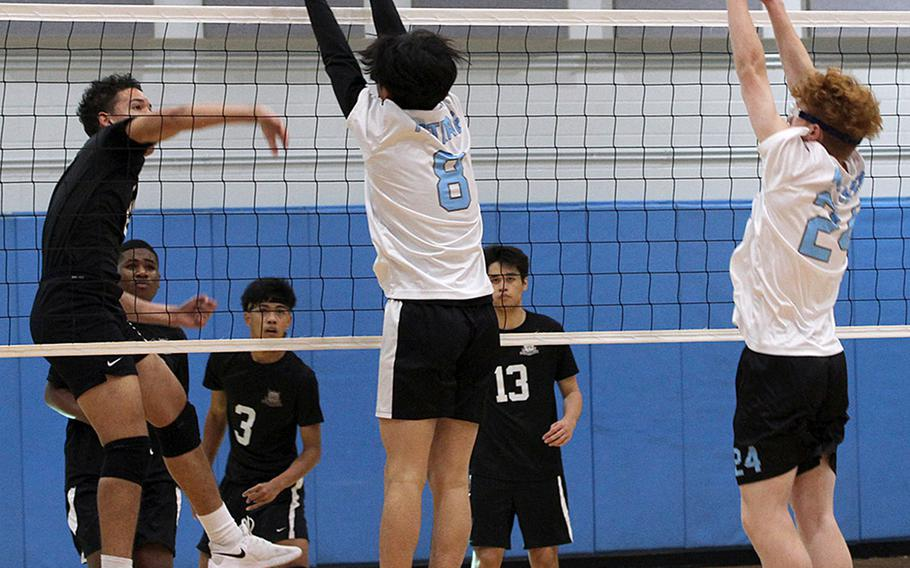 Daegu's Jordan Brown spikes against Osan's Timothy Petrae and Martin Walker during Saturday's DODEA-Korea boys volleyball match. The Cougars won 25-14, 25-21.