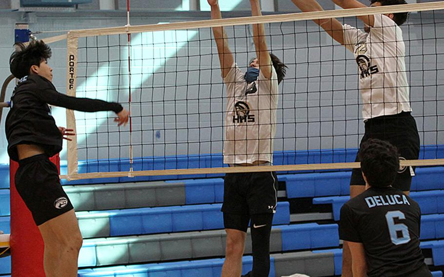 Osan's Timothy Petrae spikes through a Humphreys Gold double block of Austin Mills, center, and Collin Metcalf during Friday's DODEA-Korea district boys volleyball final. Gold won in three sets.
