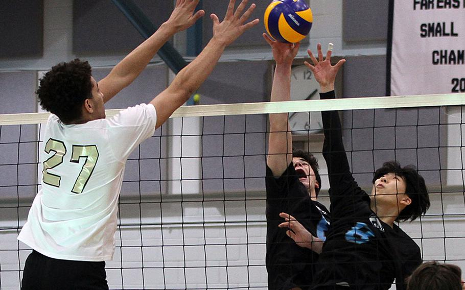 Humphreys Gold's Collin Metcalf and Osan's Timothy Petrae and Sergio DeLuca battle for the ball during Friday's DODEA-Korea district boys volleyball final. Gold won in three sets.