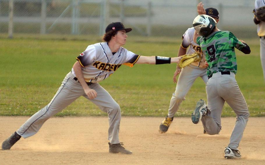 Kadena's Ethan Boerigter reaches out to tag Kubasaki baserunner Nick Patton during Thursday's Okinawa baseball game. The Dragons won 16-15.