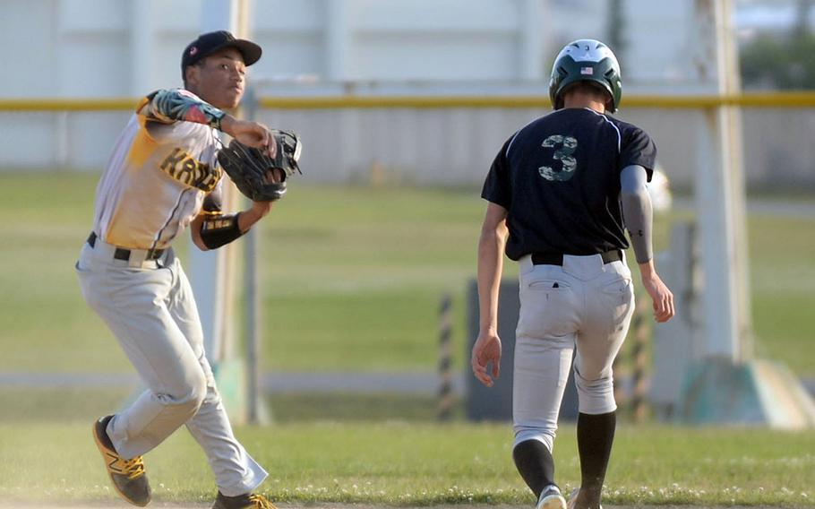 Kadena shortstop Dimitri Guy erases Kubasaki baserunner Jeffrey Owens at second base and fires a relay throw to first during Tuesday's Okinawa baseball game. The Dragons won 5-0.