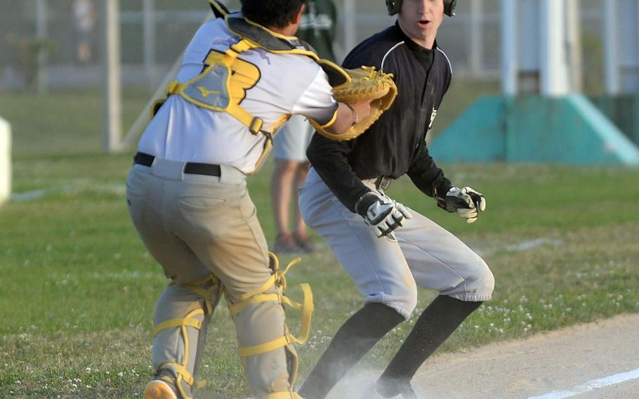Kadena catcher Jeremiah Sprague puts the tag on Kubasaki baserunner Jace Corbett in a rundown during Tuesday's Okinawa baseball game. The Dragons won 5-0.