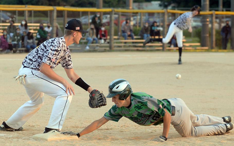 Kubasaki's Bryce Tobin dives back to the bag as Kadena's Ethan Boerigter's pickoff throw sails wide of first baseman Austin Gagnon during Thursday's Okinawa baseball game. The Dragons won 6-1.