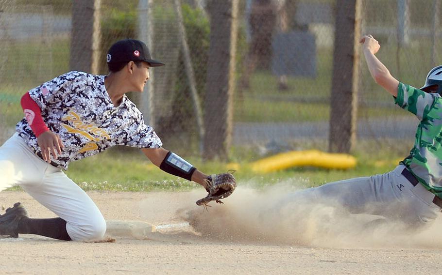 Kubasaki's Nick Patton slides safely into third base ahead of the tag by Kadena's Jake Mariano during Thursday's Okinawa baseball game. The Dragons won 6-1.