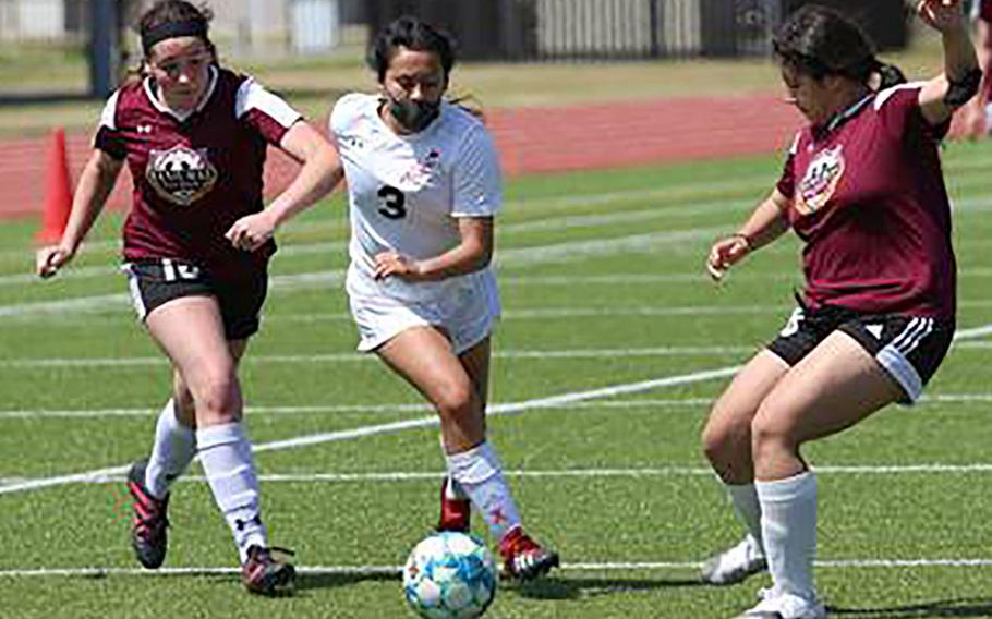 E.J. King's Alyssa Garcia dribbles between two Matthew C. Perry defenders during Saturday's DODEA-Japan girls soccer matches. The Cobras swept two matches from the Samurai.