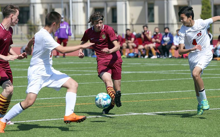 Matthew C. Perry's Gage Behnken dribbles between E.J. King defenders during Saturday's DODEA-Japan boys soccer match. The Samurai swept two matches from the Cobras.