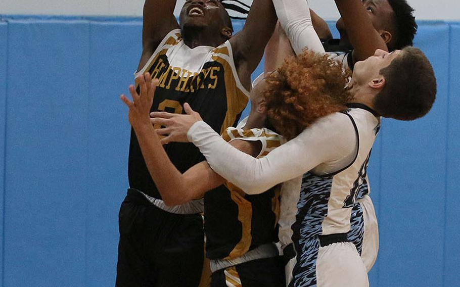 Humphreys Black's Myles Johnson reaches above a scrum of Osan Blue opponents and Blackhawks teammates for one of his 18 rebounds during Saturday's DODEA-Korea basketball game. Humphreys Black won 65-26.