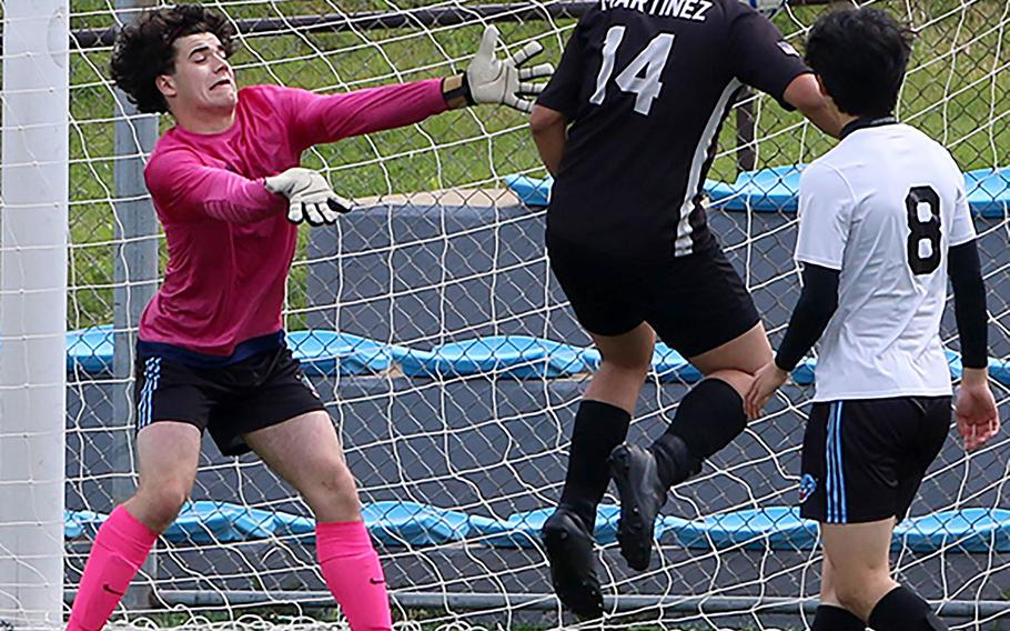 Humphreys' Juan Martinez heads the ball past Osan goalkeeper Sergio DeLuca into the net for the first goal during Saturday's DODEA-Korea boys soccer championship game. The Blackhawks won 2-0.