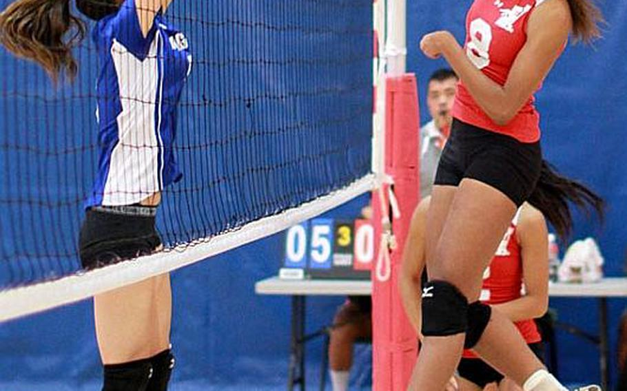 Nile C. Kinnick Red Devils' Mashiya McKinney hammers a spike kill through the block of Isabelle Charley of Christian Academy Japan Knights during Friday's semifinal match in the Far East High School Girls Division I (large schools) Volleyball Tournament at Charles King Fitness & Sports Center, Naval Base, Guam. Kinnick won 25-13, 25-14, 25-20 and advanced to Saturday's final against American School In Japan, which beat Seisen International of Tokyo 25-19, 25-22, 25-21. '