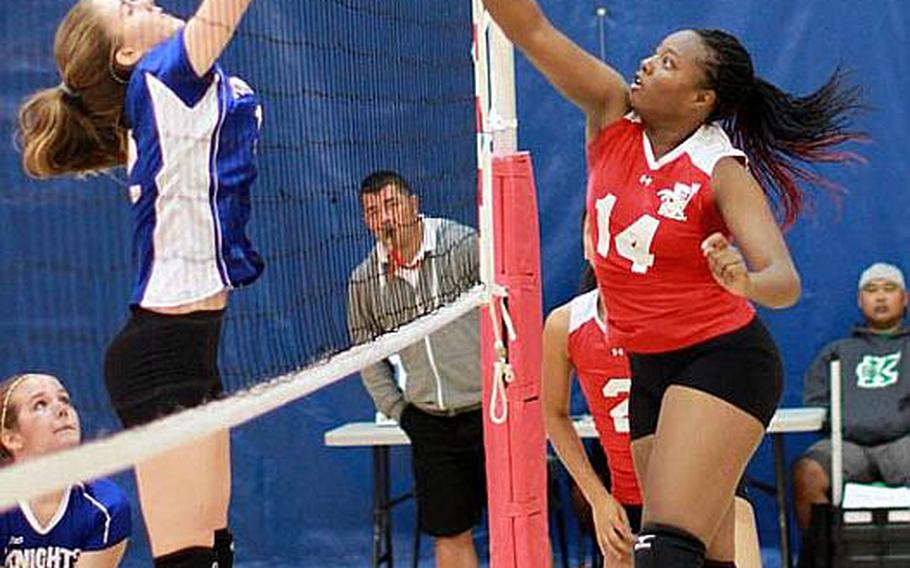 Nile C. Kinnick Red Devils' Audri Salter tries to hammer a spike kill through the block of Monica Manjarres of Christian Academy Japan Knights during Friday's semifinal match in the Far East High School Girls Division I (large schools) Volleyball Tournament at Charles King Fitness & Sports Center, Naval Base, Guam. Kinnick won 25-13, 25-14, 25-20 and advanced to Saturday's final against American School In Japan, which beat Seisen International of Tokyo 25-19, 25-22, 25-21.