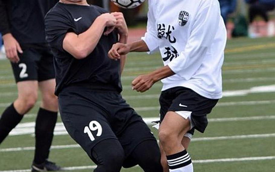 Zama's Rain-Kai Thompson and Okinawa Christian's Shin Lewis battle for control during Monday's pool-play match in the Far East Division II Boys Soccer Tournament. The teams tied 1-1.