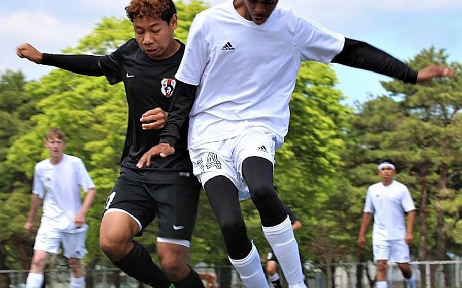 Zamas Justyn Seraphin and Robert D. Edgren's Antonio DeVaughn battle for the ball during Wednesday's playoff game in the Far East Boys Division II Soccer Tournament, won by the Trojans 6-0.  CAITLIN BLOUNT/SPECIAL TO STRIPES